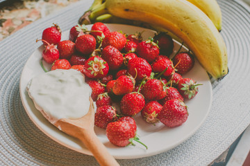 Bunch of bananas and strawberries. Photo toned style Instagram filters. Concept of healthy breakfast