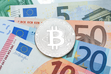 Silver Bitcoin close-up. Background euro currency. Conceptual photo.