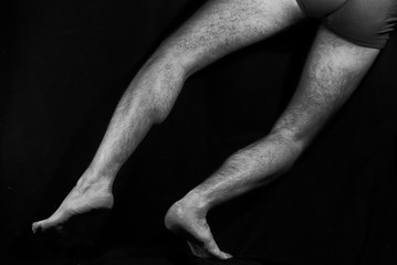 Beautiful, muscular, bare male feet on a black background