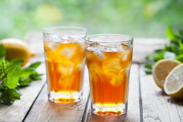 Ice tea summer refreshing cocktail drink on wooden table with a view to the terrace and trees. Close up summer antioxidant beverage. A frozen glass. Cold longdrink or lemonade