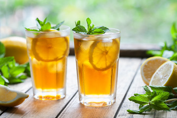 Iced tea with lemon slices and mint on wooden table with a view to the terrace and trees. Close up summer vitamin antioxidant beverage. A frozen glass. Copy space for text. Cold longdrink or lemonade