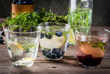 Summer refreshment diet drinks. Infused detox waters in different glasses nd bottles with rosemary, lime and blueberries, lemon and tarragon. Rustic wooden old table Copy space