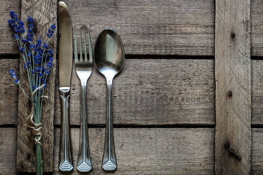 A bouquet of lavender and a set of steel cutlery (fork, spoon, knife) on a wooden background