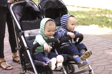two boy twins in a stroller in the street