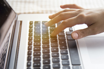 woman's hands using laptop with blank screen on table in offie