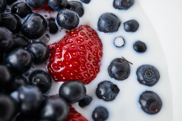 Strawberries, blueberries and milk in a white bowl