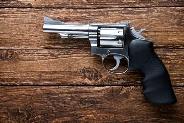 Gun on wooden background. top view