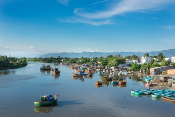 Vietnam in the morning. Traditional Vietnamese boats, fishing boats on the river, cloudy blue sky.