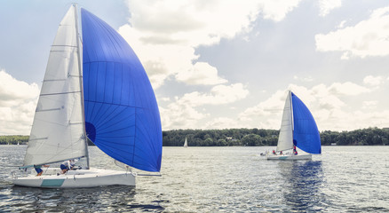 Boat with big blue spinnaker sail.  Sailing yacht race. Match race.  Team athletes participating in the sailing competition
