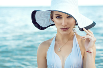 Close up portrait of gorgeous elegant glam lady wearing white bra, wide-brimmed hat and golden chain with pendant at the seaside looking straight. Vogue concept. Copy space