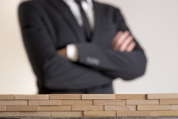 Businessman with folded arms with wall of wooden bricks infront of him