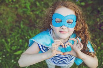 Superhero girl showing hands in heart shape.
