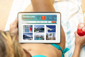 Young woman in a bikini visiting a travel website  at her tablet device, lying on a beach towel and having a drink