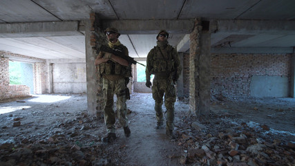 Two men in special clothing holding guns and walking slowly inside of ruined building.