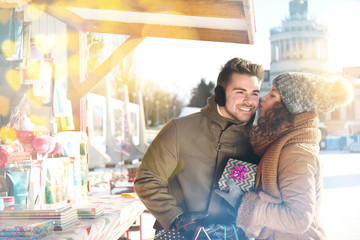 Man presenting gift to woman on Christmas market