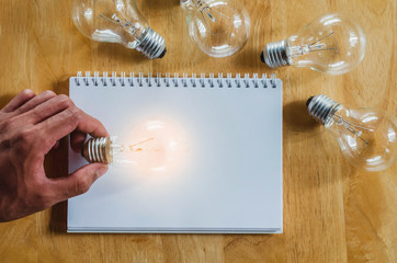 concept hand and light bulb isolate on notebook background