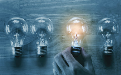 concept hand and light bulb isolate on wood background