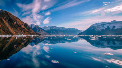 Clouds reflected in blue water of Greenland fjord surrounded by snow capped peaks.