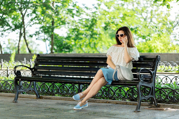 Young woman in a park in a white blouse and blue skirt is sitting on a bench and talking on a mobile phone.