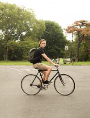 Full figure shot of modern Caucasian college student riding bike in the park