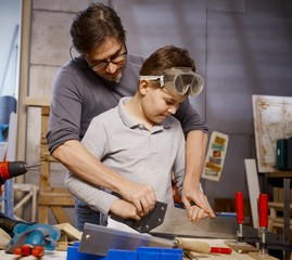 Father and son using saw