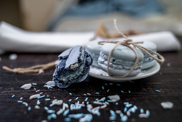 Blue and sea blue macaroons in a marine theme on a dark background decorated with rope and sea salt.