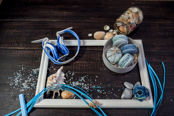 Food decorating with sea details such as shells, stones, salt, rope on wood background with blue ribbon