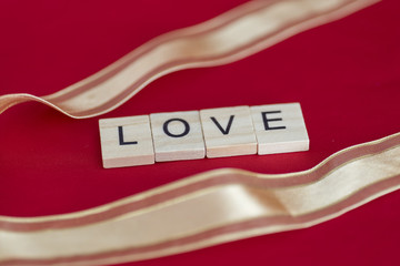 """""""LOVE"""" Wooden letters on red background with golden ribbon"""