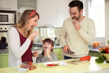 Young family preparing salad together.