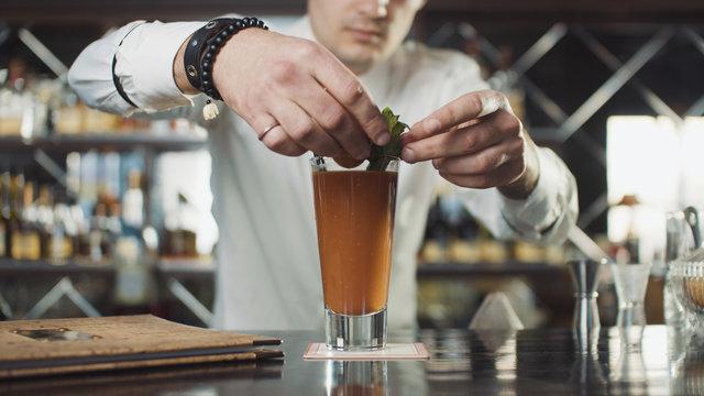 Bartender in hat is preparing cocktail in bar