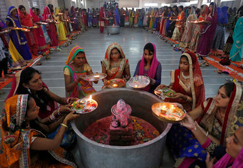 Hindu women perform a ritual known as Aarti around a Shivling (a symbol of Lord Shiva) on the last day of Jaya Parvati Vrat festival in Ahmedabad