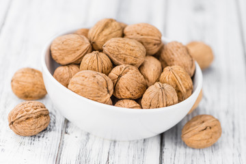 Portion of Whole Walnuts on wooden background (selective focus)
