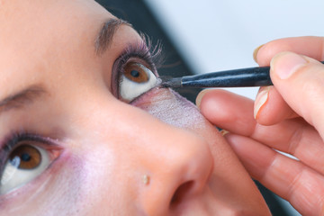 Makeup. Make-up Applying closeup. Eyeliner. Cosmetic Eyeshadows. Eyeline brush for Make up
