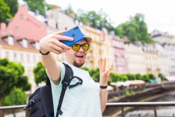 Handsome man is taking a selfie outdoor - caucasian people - nature, people, lifestyle and technology concept.