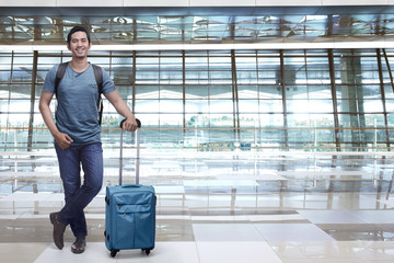 Handsome asian man backpacker holding blue suitcase
