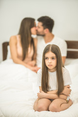 The sad girl sit near the kissing parents on the bed