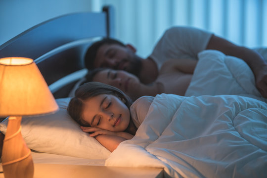The little girl sleeping near the parents in the bed. night time