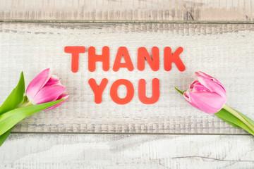 Danke in roten Buchstaben mit zwei Tulpen auf Holzhintergrund