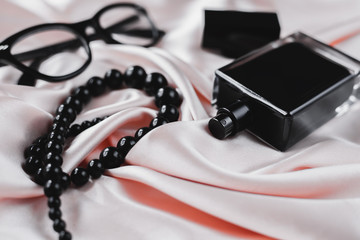 Fashion female accessories. Perfume with beads and sunglasses