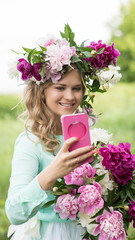 Portrait. Beautiful smiling woman wearing a wreath and a bouquet of peonies holding a pink phone and taking a selfie