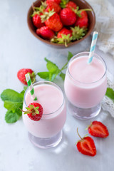 Freshly squeezed strawberry berry cocktail in a glass jar on a gray stone or slate background. Superfoods and health or detox diet nutrition concept.