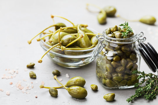 Mixed capers in jar and bowl on white kitchen table.
