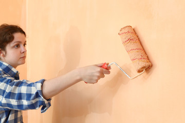 Young worker painting wall in a room to orange using paint roller