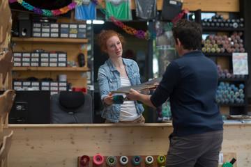 Woman working in skateboard shop, handing skateboard to customer