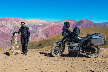 Woman standing next to touring motorbike at the colourful mountains of Humahuaca, 4,300m altitude, Jujuy, Argentina, South America
