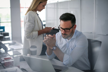 Two business people watching something on laptop. Business woman showing something to colleague in laptop.