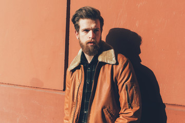 Portrait of cool young bearded man leaning against orange wall
