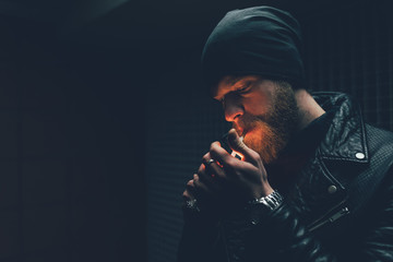 Young male hipster in knit hat igniting cigarette at night