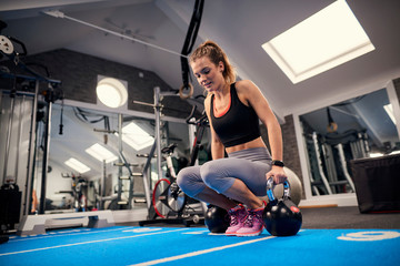 Young woman training, preparing to lift kettle bells in gym