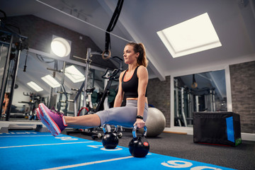 Young woman training, doing sit up push ups on kettle bells in gym